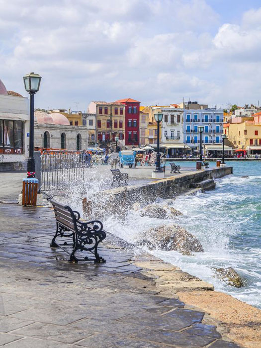 Bench on the waterfront with splashing waves in Chania, Crete